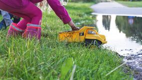Mud Industries. Children playing in the grass and mud with a dump truck Royalty Free Stock Images