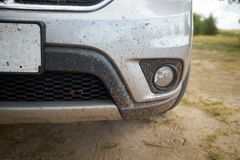 Mud and insect splattered front bodywork of a car. Mud and insect splattered front bodywork of a sliver car parked on a dirt road in the countryside in a close Stock Photos