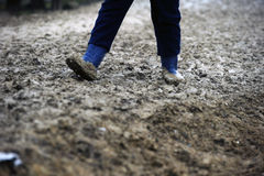 Mud. Man walking in the mud with rubber boots Stock Photography