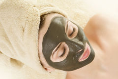 Mud Mask on the face.Spa. Beautiful Young Woman applying a Mud Mask.Spa and facial care concept Royalty Free Stock Photography