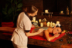Mud mask of woman in spa salon. Back massage . Mud mask of women in spa salon. Back massage with clay full body . Girl on interior with candles in oriental stock photography