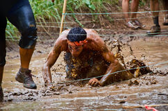 Mud race participant crawling through a mud pit Stock Photography