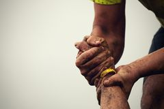 Mud race runners. Couple hold hands,help when overcoming hindrances mud Royalty Free Stock Photography