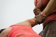 Mud race runners. Couple hold hands,help when overcoming hindrances mud Stock Photography
