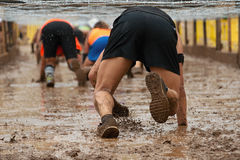 Mud race runners. Crawling,passing under a barbed wire obstacles during extreme obstacle race Stock Photo