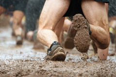Mud race runners. Crawling,passing under a barbed wire obstacles during extreme obstacle race Royalty Free Stock Photos