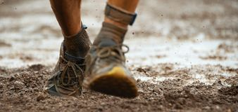 Mud race runners. Detail of the legs,muddy running shoes after a run in the mud Royalty Free Stock Photography