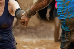 Mud race runners. The man helps the woman to overcome the obstacle Royalty Free Stock Images