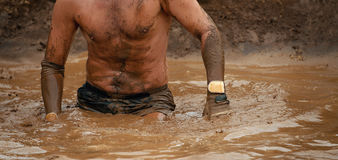Mud race runners. Obstacle race runner in action Royalty Free Stock Photography
