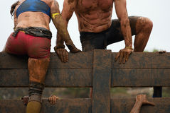 Mud race runners. Participants overcome obstacles Stock Image