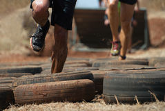 Mud race runners. Tries to make it through the tire trap Stock Image