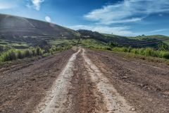 Mud road with tire marks runs through green valley in Malanje. Angola. Africa. Africa stock image