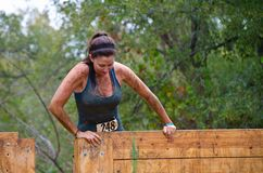 Mud run racer at obstacle stock image