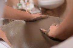 Mud skin treatment. Woman enjoying a mud skin treatment in a Spa Stock Photo