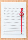 Blank sheet music end a red pencil in the shape of treble clef. Composing concept. Royalty Free Stock Images