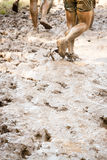 Mud Trail Run. Group of runners on a muddy trail. The image orientation is vertical and there is copy space Royalty Free Stock Photography