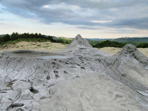 Mud volcano. Big and small mud volcano eruption. Dried out grey dirt covered with cracks royalty free stock photos