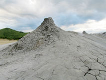 Mud volcano. Big and small mud volcano eruption. Dried out grey dirt covered with cracks royalty free stock images