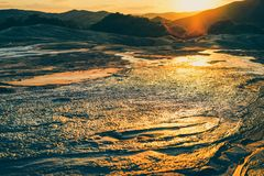 Mud volcano in Buzau, Romania. Mud flowing from muddy volcano with beautiful sunset in the background, Berca, Buzau, Romania Stock Photography