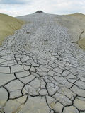Mud volcano. Crater erupting with dirt. Dried out grey dirt covered with cracks and crannys on a cloudy day in summer stock photos