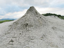 Mud volcano erupting with dirt. Vulcanii Noroiosi de la Paclele Mici and Mari – mud volcanos in Buzau. Dried out grey dirt covered with cracks and stock photos