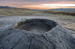 Bubbling mud. Mud volcano at sunset - landmark attraction in Buzau, Romania Stock Photo