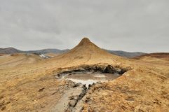 Mud Volcanoes and a sky with clouds Royalty Free Stock Photos