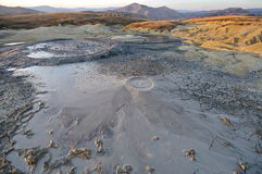 Bubbling mud. Mud volcano at sunset - landmark attraction in Buzau, Romania Royalty Free Stock Image