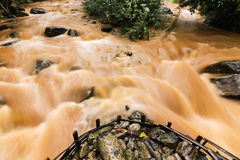 Mud and water pouring down  after very heavy rain. Edge of large powerful muddy brown waterfall rapids flowing and splashing Stock Photo