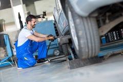 Mudança de roda do carro pelo mecânico fotos de stock