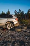 Mudança do pneu em um campo do cascalho com jaque foto de stock