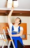 Mudança nova do funcionamento do eletricista um bulbo em casa Imagem de Stock