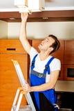 Mudança nova do funcionamento do eletricista um bulbo em casa Imagens de Stock Royalty Free