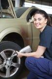 Mudança feliz do pneu do mecânico da mulher Imagens de Stock