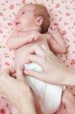 Mudando o tecido de um bebê fotografia de stock