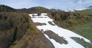 Mudanza adelante del descubrimiento sobre bosque de maderas del alerce del pino y pista nevosa del esquí en montaña en otoño Mont almacen de metraje de vídeo
