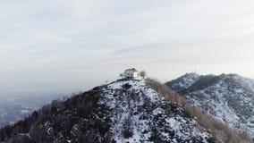Mudanza adelante a la construcción o a la iglesia sobre el top de la montaña nevosa en otoño o invierno en la puesta del sol Bosq almacen de video