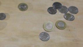 Mudanza del vídeo del valor del dinero la moneda tiene arrojar a chorros en el tablero almacen de metraje de vídeo