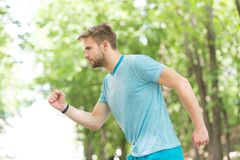 Mudanza a su meta Sirva el funcionamiento joven confiado en parque, vista lateral El deportista ambicioso se mueve para alcanzar  foto de archivo libre de regalías