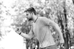 Mudanza a su meta Sirva el funcionamiento joven confiado en parque, vista lateral El deportista ambicioso se mueve para alcanzar  foto de archivo
