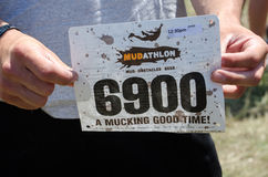 Mudathlon contestant number. A participant in the 2012 mudathlon in Indiana holds up his race number before he pins it to his shirt Royalty Free Stock Images