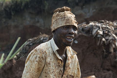 Mudbrick former in Uganda. Bedraggled worker preparing bricks from clay by hand in Uganda Royalty Free Stock Photos