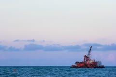 Muddra sandskeppet som arbetar i havet i blå himmel Royaltyfria Foton