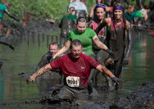 Muddy active people. Active people of all ages, make thier way through the thick mud, during the July 2014 mudathlon in northwest Indiana Royalty Free Stock Images
