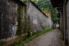 Muddy alleyway between ancient dwelling houses Stock Photo