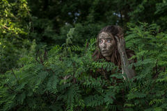 Muddy Amazon girl hiding behind a bush in the woods Stock Photos
