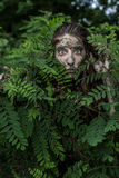Muddy Amazon girl hiding behind a bush in the woods Royalty Free Stock Photography