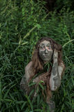 Muddy Amazon girl hiding behind a bush in the woods Royalty Free Stock Images