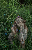 Muddy Amazon girl hiding behind a bush in the woods, while soap bubbles flying around her Royalty Free Stock Photography