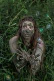 Muddy Amazon-Mädchen, das sich im Wald hinter einem Busch, während Seifenblasen fliegen um sie versteckt Lizenzfreie Stockfotografie